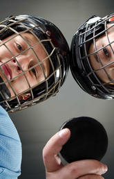 image of two kids wearing hockey gear holding a puck