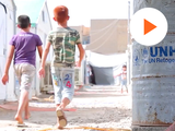 image of two kids walking in a refugee camp