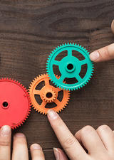 image of hands placing plastic gears on a table