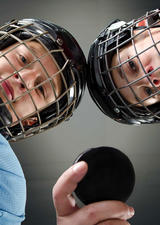 photo of two kids in hockey uniforms holding a puck